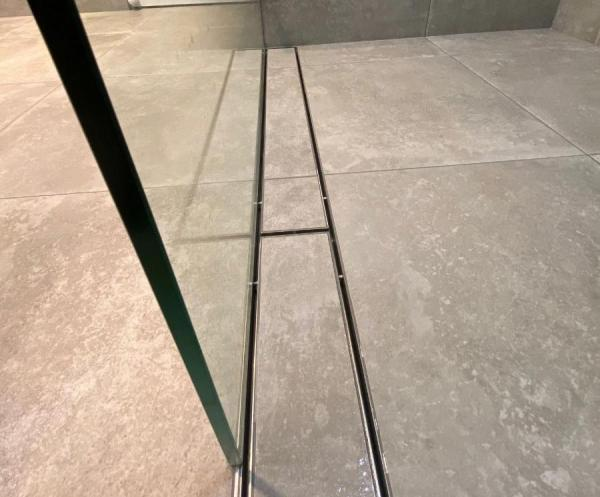 Where should a linear shower grate be placed?